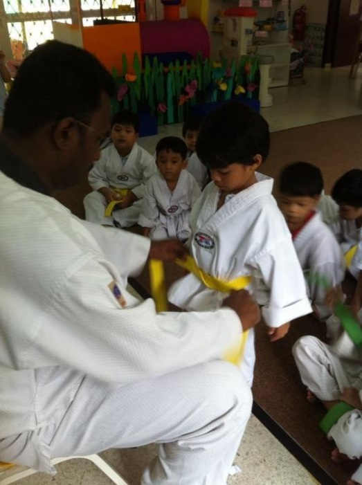 receiving his new yellow belt!